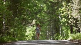 Młodzi miedzianowłosi dziewczyna bieg przez lasowej Pięknej dziewczyny iść wewnątrz dla sportów i monitorują zdrowie swobodny ruc zbiory