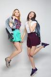 młodzi modniś dziewczyn najlepsi przyjaciele skaczą Obrazy Royalty Free
