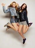 młodzi modniś dziewczyn najlepsi przyjaciele skaczą Obrazy Stock