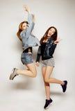 młodzi modniś dziewczyn najlepsi przyjaciele skaczą Obraz Royalty Free