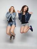 młodzi modniś dziewczyn najlepsi przyjaciele skaczą Zdjęcie Stock