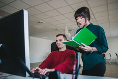 Młodzi modnisiów koledzy w biurze przy komputerem Młodość today który pracuje w biurze Obrazy Royalty Free