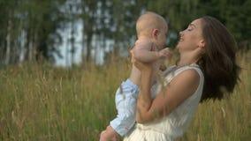 Młodzi mum chwyty na rękach jej mały dziecko zbiory