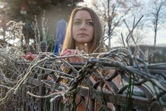 Młodzi nadzy kobieta stojaki w ogródzie w zimie na ciskającym żelazie one fechtują się z mrozowym hoarfrost obrazy royalty free
