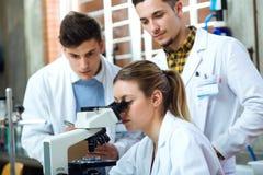 Młodzi naukowowie niesie out eksperyment w laboratorium zdjęcia stock