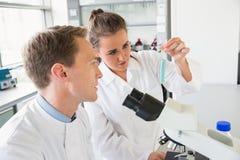 Młodzi naukowowie pracuje wraz z próbną tubką zdjęcia stock