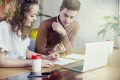 Młodzi partnerów biznesowych ludzie zbierali wpólnie, dyskutujący kreatywnie pomysł w biurze Używać nowożytnego laptop, mieć kawę Zdjęcia Royalty Free