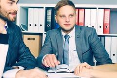 Młodzi partnery biznesowi dyskutuje pomysły dla rozpoczęcia przy spotkaniem Partnery biznesowi używa laptop i dyskutować nowy obraz stock