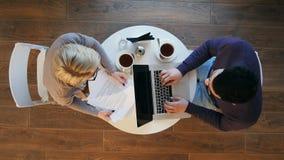 Młodzi partnery biznesowi siedzi przy round stołem w kawiarni i działaniem na projekcie obraz stock
