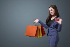 Młodzi piękni azjatykci kobiety mienia torba na zakupy i pokazują jej c Obraz Stock