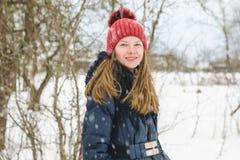 Młodzi piękni jasnogłowi dziewczyna stojaki, uśmiechy w parku pod miękkim puszystym śniegiem na zimnym zima dniu i obrazy stock