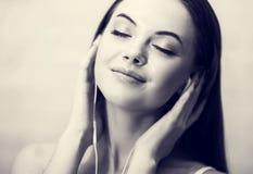 Młodzi piękni kobieta hełmofony słucha muzyczny czarny i biały Fotografia Stock