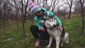 Młodzi piękni kobieta spacery, sztuki z jej husky psem przy zimą wokoło lasu i zdjęcie wideo