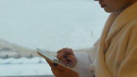 Młodzi, piękni kobieta stojaki okno, i wysyłają wiadomości od jej telefonu komórkowego zbiory
