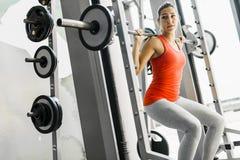 Młodzi piękni kobieta udźwigu ciężary w gym Fotografia Stock