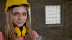 Młodzi piękni uśmiechnięci dziewczyna budowniczego chwyty w rękach jej smartphone, watchig przy kamerą, komunikacyjny pojęcie zbiory