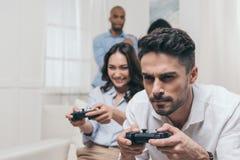 Młodzi przyjaciele bawić się wideo gry w domu zdjęcia stock