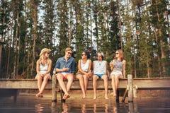 Młodzi przyjaciele cieszy się dzień przy jeziorem Fotografia Royalty Free