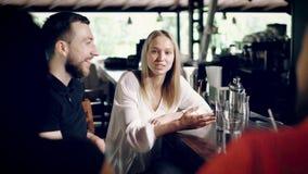 Młodzi przyjaciele które siedzą na prętowych stolec blisko boron kontuaru komunikują z each inny, ładna blondynka mówją śmieszneg zbiory wideo