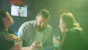 Młodzi przyjaciele ma zabawę blisko zgłaszają z kolorowymi napojami w dymu na tle barwione lampy przy przyjęciem zbiory