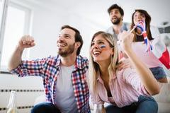 Młodzi przyjaciele ogląda TV i rozwesela piłkę nożną obrazy royalty free