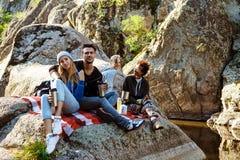 Młodzi przyjaciele siedzi na skale w jarze, ono uśmiecha się, pijący herbaty obraz royalty free
