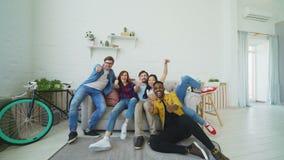 Młodzi przyjaciele uśmiecha się aprobaty wszystko bieg i doskakiwanie na kanapie pokazuje wpólnie w domu i zbiory
