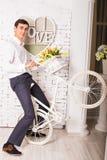 Młodzi przystojni mężczyzna w białym wnętrzu z bicyklem Obrazy Stock