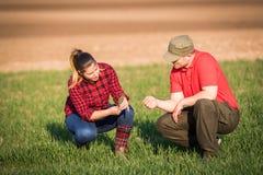 Młodzi rolnicy examing uprawianej banatki podczas gdy ciągnik orze fi Fotografia Stock