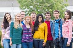 Młodzi studenci collegu stoi w parku obrazy stock