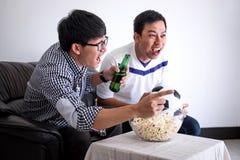Młodzi Szczęśliwi Azjatyccy mężczyzna rodzina lub fan piłki nożnej ogląda piłkę nożną ma obrazy stock