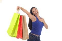 Młodzi szczęśliwi i piękni latynoscy kobiety mienia koloru torba na zakupy uśmiecha się excited odosobnionego fotografia stock