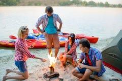 Młodzi Szczęśliwi podróżnicy Odpoczywa przy wieczór blisko Podpalają na piasek plaży Przed kajakami, namiotem i rzeką, Zdjęcie Royalty Free