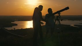 Młodzi szczęśliwi przyjaciół spojrzenia przy lato zmierzchem na widoku teleskop i mieć zabawę zdjęcie wideo