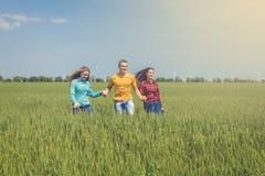 Młodzi szczęśliwi przyjaciele biega na zielonym pszenicznym polu Zdjęcia Royalty Free