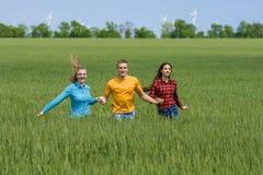 Młodzi szczęśliwi przyjaciele biega na zielonym pszenicznym polu Obrazy Royalty Free