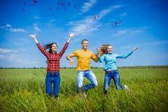 Młodzi szczęśliwi przyjaciele biega na zielonym pszenicznym polu Zdjęcie Stock
