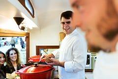 Młodzi szef kuchni porci klopsiki dwa ładnej dziewczyny w jedzeniu przewożą samochodem Obraz Stock