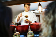 Młodzi szef kuchni porci klopsiki dwa ładnej dziewczyny w jedzeniu przewożą samochodem fotografia royalty free