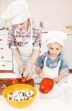Młodzi szefa kuchni narządzania warzywa w kuchni fotografia royalty free