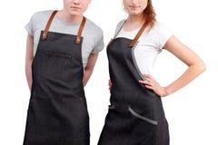 Młodzi szefowie kuchni, kelnery mężczyzna lub kobiety pozować, jest ubranym fartuchy na białym tle zdjęcia royalty free
