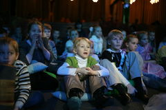 Młodzi teatromany dzieci entuzjastycznie ogląda children kukiełkowego przedstawienia Bożenarodzeniowego theatre Smeshariki Obrazy Royalty Free