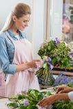 Młodzi uśmiechnięci kwiaciarni mienia ułożenia i bukieta kwiaty w kwiatu sklepie Fotografia Royalty Free