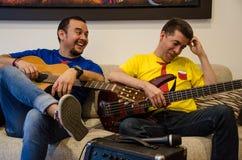Młodzi uśmiechnięci ludzie bawić się gitary siedzi na kanapie zdjęcie stock