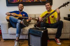 Młodzi uśmiechnięci ludzie bawić się gitary siedzi na kanapie w domu obraz royalty free