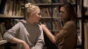 Młodzi ucznie siedzi i opowiada między półkami na książki zdjęcie wideo