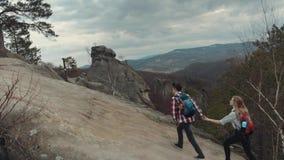Młodzi wycieczkowicze chodzi na wysokiej góry wzgórzu w burzowej, wietrznej pogodzie, Pomaga dziewczyny wspinać się up, trzymając zbiory