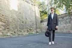 Młodzi, wysocy, fachowi biznesmenów spacery, zestrzelają ulicę w żakiecie z klasyczną teczką zdjęcia stock