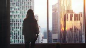 Młodzi zadumani kobieta stojaki duży nadokienny przyglądającym out jej mieszkanie na miasto budynkach podczas zmierzchu swobodny  zdjęcie wideo