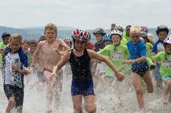 Młodzieżowi triathlon biegacze przy aquelle Mudman seriami fotografia royalty free